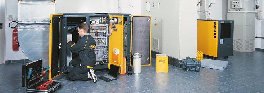 technician performing maintenance on an air compressor